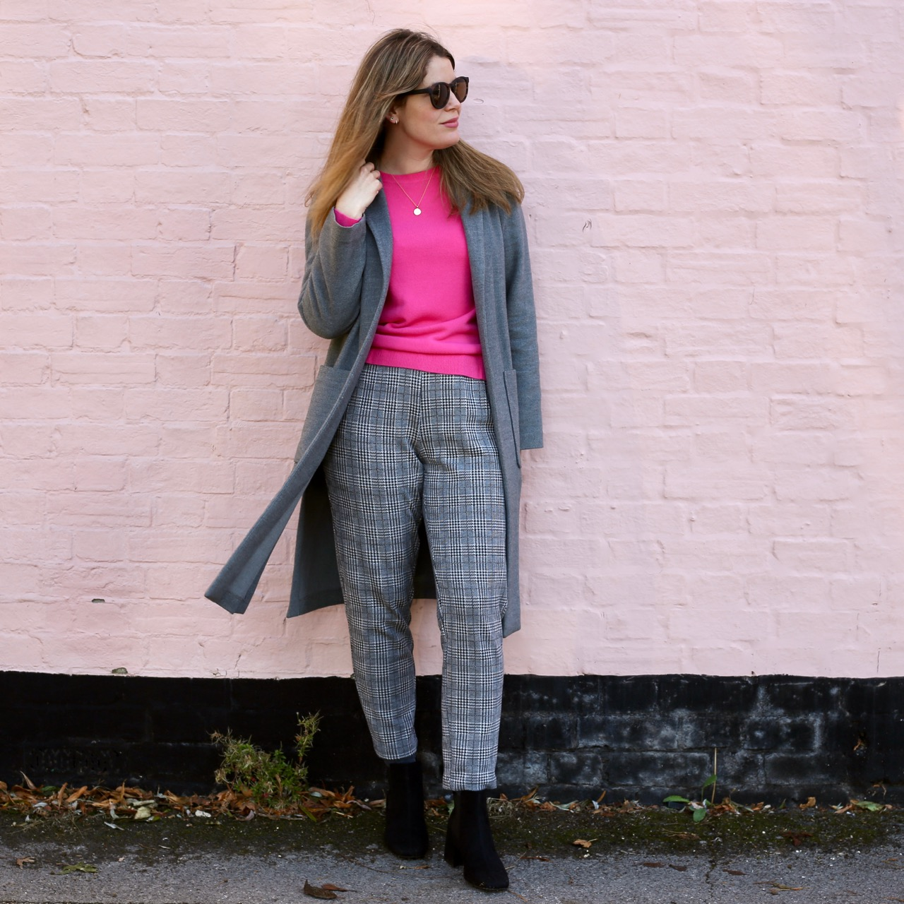 Pink jumper and grey trousers