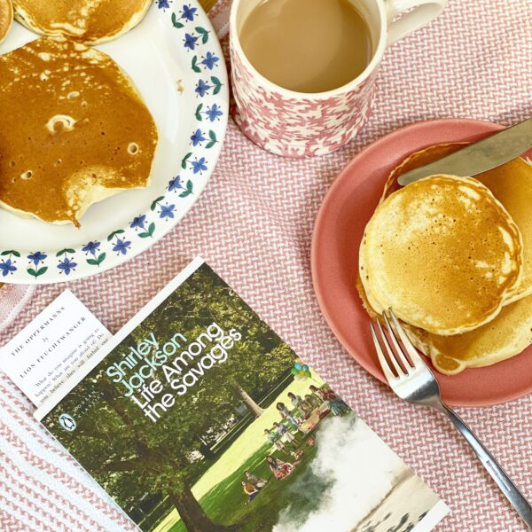Book at the breakfast table of pancakes and tea